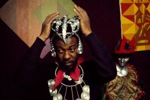 Edfu Kinginga with wall art by Eileen Abdulrashid, Omar Lama, hat and dance costume by Max Fran Smith on mannequin by Yaounde Olu