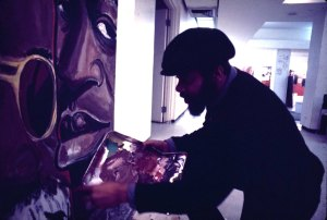 Mitchell Caton painting an unidentified indoor mural. Photo by Mark Rogovin, Public Art Workshop Mural Archive.